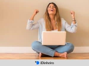 mulher com laptop comemorando pois aprendeu como investir na bolsa de valores