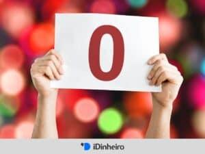 mãos segurando um cartaz com o número zero, representando corretoras corretagem zero
