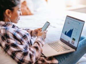 Imagem de uma mulher de blusa xadrez e calça jeans sentada na cama usando o celular e o notebook para pedir empréstimo para empresa online