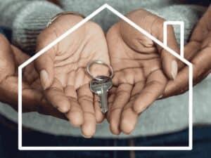 mãos segurando chave dentro de figura de casa, representando financiamento imobiliario selic
