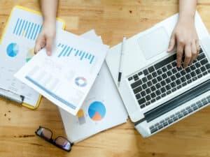 O que é gestão financeira: Imagem de uma pessoa usando notebook e vendo papéis com gráficos