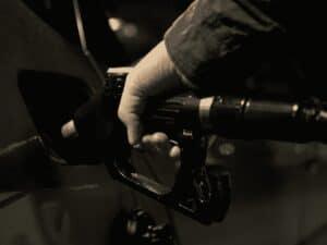 mão segurando bomba de combustível para abastecer carro, representando icms combustíveis