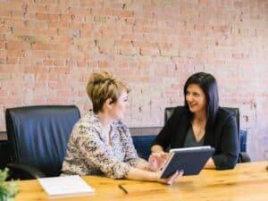 melhor banco para abrir conta jurídica: imagem de duas mulheres em uma mesa e conversando