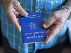 pessoa segurando carteira de trabalho, representando pagamento do benefício emergencial