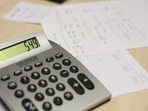 calculadora e papéis em cima de mesa representando prorrogação de prazo do IR