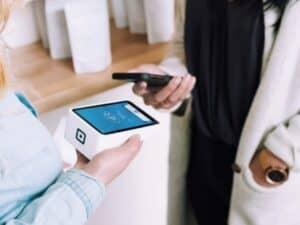 Imagem de uma pessoa segurando uma máquina de cartão e outra um celular para representar qual a melhor máquina de cartão de crédito para autônomo