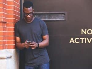 homem encostado em parede acessando smartphone representando smartphone com melhor custo-benefício