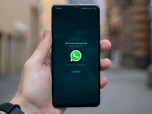 WhatsApp Pay: imagem de uma pessoa segurando um celular com o ícel do WhatsApp
