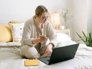 Imagem de uma mulher sentada em sua cama. Ela está usando um computador, tem um caderno ao seu lado e segura o celular com uma das mãos. Usamos a imagem para representar nosso conteúdo sobre como baixar o app Bradesco Cartões
