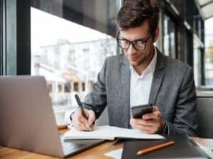 imagem para ilustrar o artigo sobre bb empresas de um homem com um celular na mão enquanto escreve em um caderno