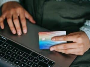 Imagem de uma pessoa usando um notebook e segurando o seu cartão de crédito. Usamos para representar o nosso post sobre cancelar compras no cartão de crédito