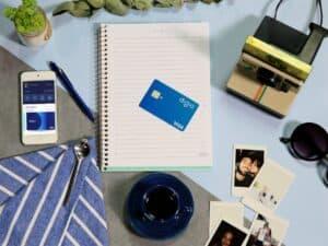 Imagem de uma mesa com vários objetos, entre eles um celular aberto no app do Digio e um cartão de crédito. Usamos essa imagem para representar nosso conteúdo que avalia se o cartão Digio é bom