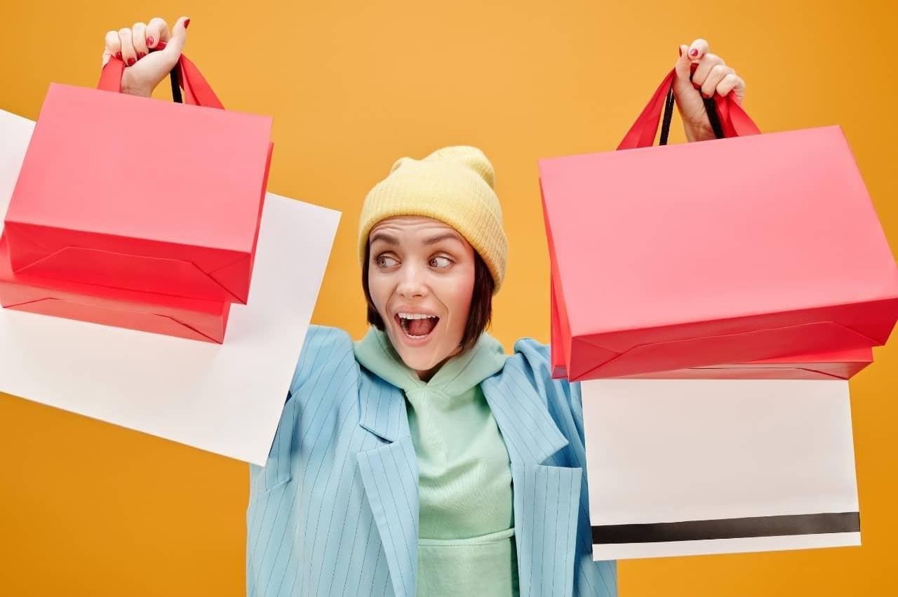 mulher feliz carregando várias sacolas