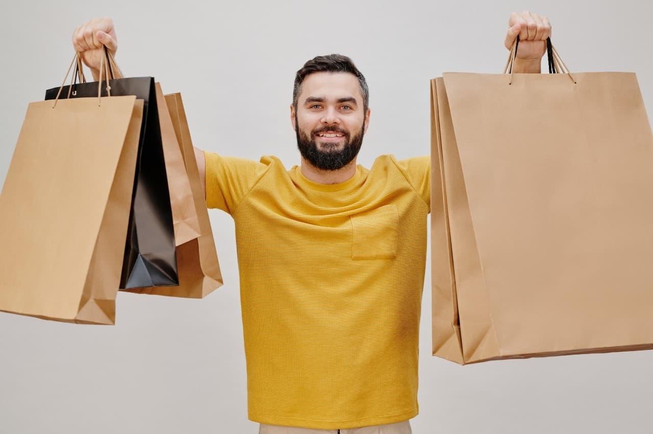 homem consumista carregando várias sacolas