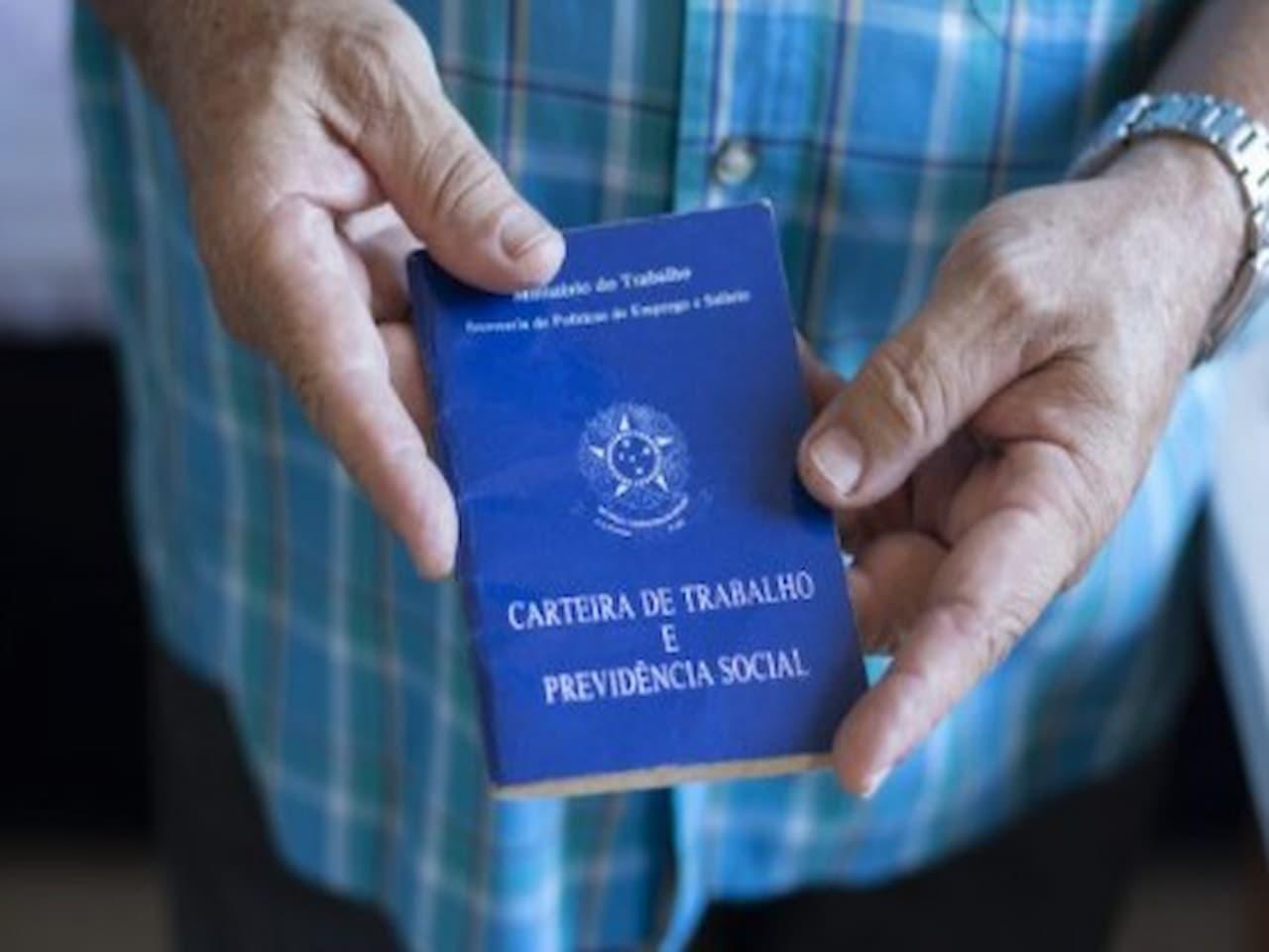 pessoa mostrando carteira de trabalho em suas mãos representando desemprego em fevereiro-abril