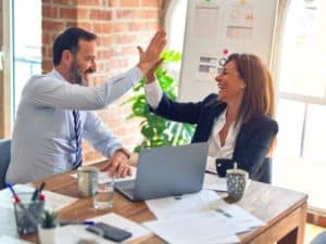 empréstimo para MEI online: duas pessoas tocando as mãos e comemorando