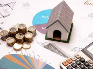 Maquete de casa, moedas empilhadas, calculadora e documento com gráficos, representando renegociação ou portabilidade
