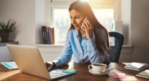 imagem de uma mulher usando o computador enquanto fala ao telefone para pedir empréstimo para MEI Santander