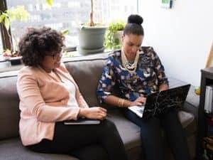 empréstimo para abrir empresa: imagem ilustrativa de duas mulheres sentadas num sofá e uma delas com computador no colo