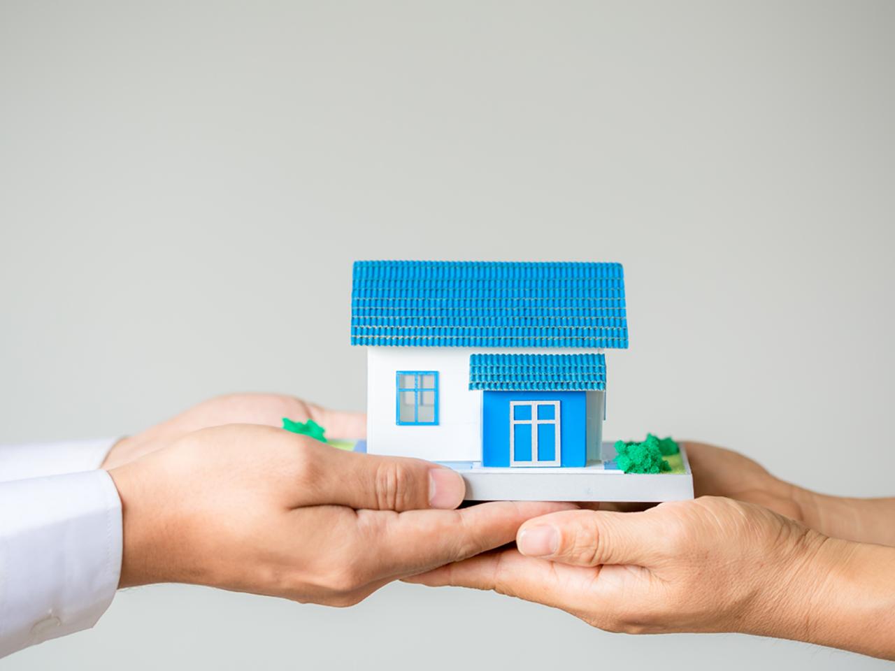 mãos segurando maquete de casa, representando feirão digital da casa própria