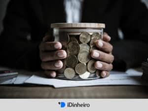 homem segurando pote de moedas representando fundos de investimento