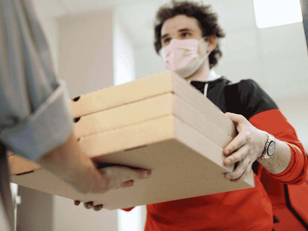 homem entregando caixas de pizza, representando gastar menos com delivery