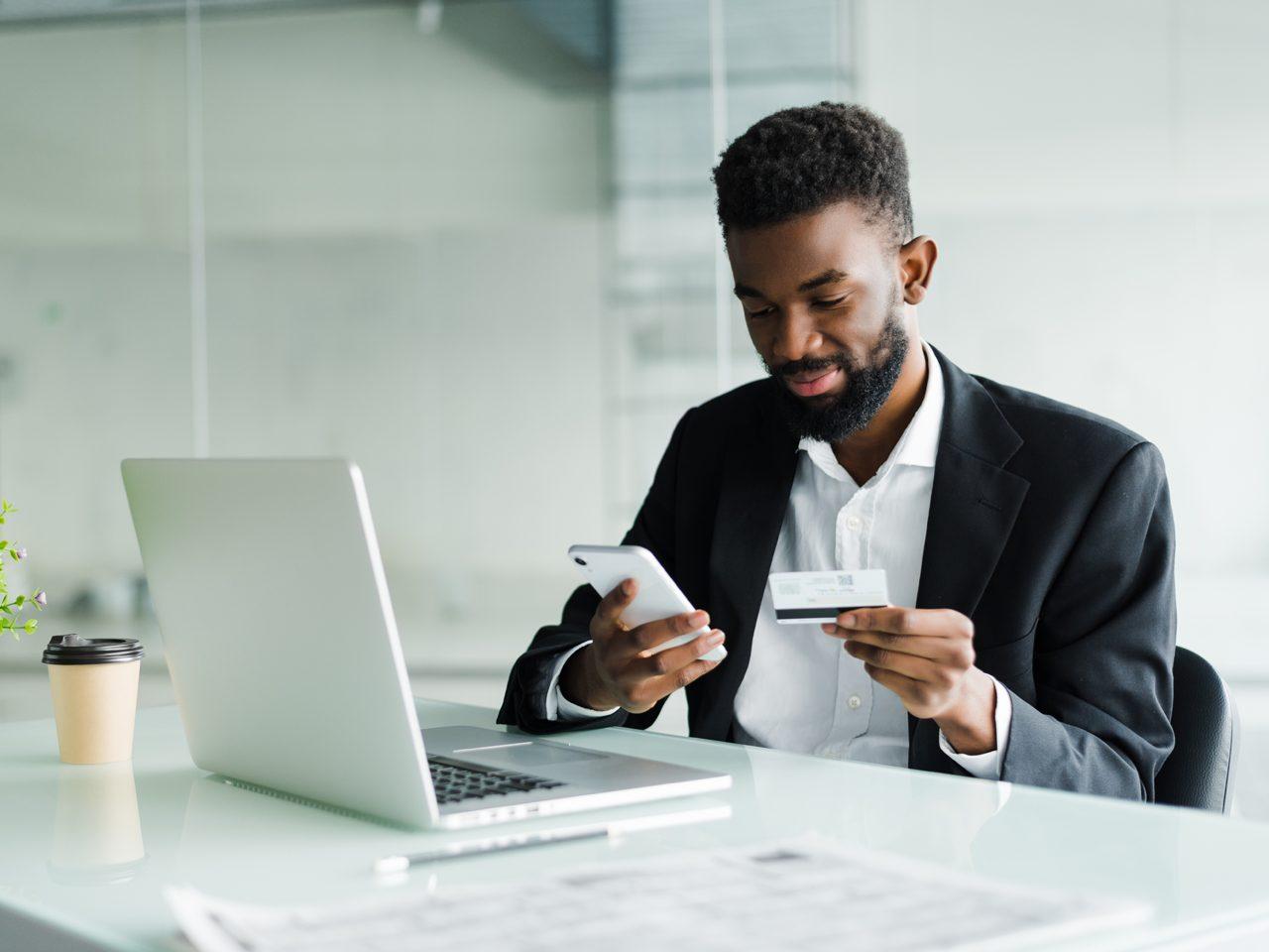 homem segurando cartão e celular, representando investimentos cartão de crédito
