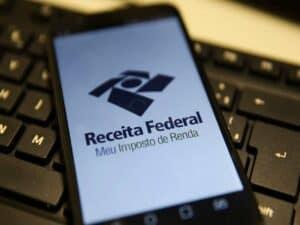 celular com tela aberta no aplicativo da Receita Federal colocado em cima de teclado de computador representando malha fina do IR 2021