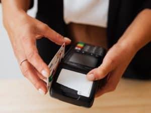 uma mulher pagando em uma máquina de cartão para MEI