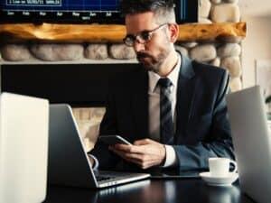 imagem de um homem com um celular na mão e olhando um computador para escolher o melhor banco para abrir conta MEI