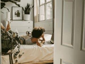 mulher deitada na cama com cachorro, representando morar sozinho