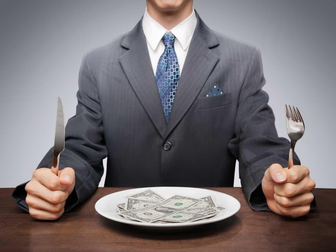 homem segurando garfo e faca com notas de dinheiro em seu prato, simbolizando consumismo