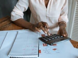 mulher faz cálculos em calculadora com bloco de anotações ao lado representando pagamento de crédito imobiliário