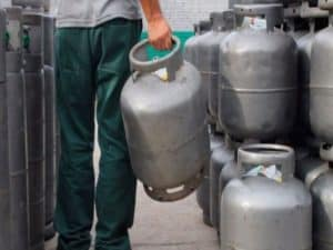 homem de costas segurando botijão no meio de outros botijões representando preço do gás de cozinha