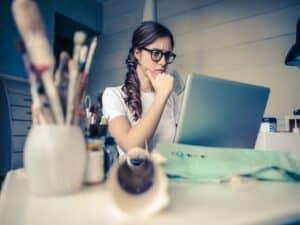 mulher na frente do notebook com semblante preocupado com financiamento de carro atrasado, busca e apreensão