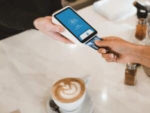 qual a melhor máquina de cartão com menor taxa: imagem de uma pessoa pagando com uma máquina de cartão e uma xícara de café ao lado