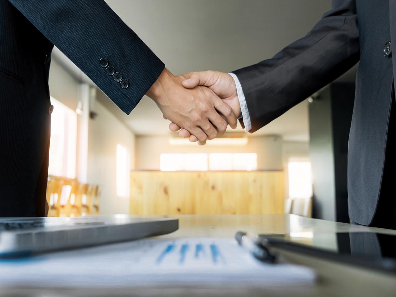 seguro empresarial: imagem de dois homens de terno apertando as mãos