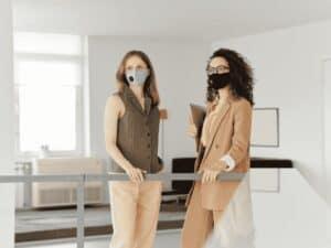duas mulheres de máscara de volta ao trabalho presencial