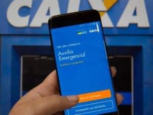 Mão segurando celular com o site do auxílio emergencial aberto e uma agência da Caixa ao fundo, representando 5ª parcela do Auxílio Emergencial.