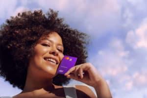 mulher segura cartão nubank próximo ao rosto. a imagem representa a necessidade de aumentar limite
