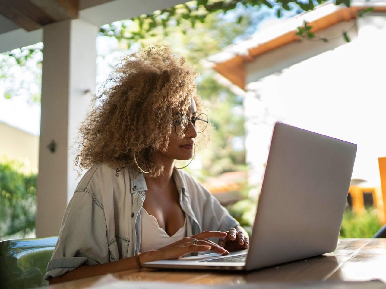 Mulher mexendo no notebook representando programa da MRV, que oferece 10 mil bolsas para cursos online de tecnologia
