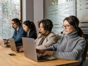 PagSeguro telefone: imagem ilustrativa de uma central de atendimento com pessoas com fone de ouvido usando notebook
