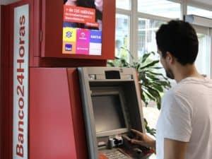 Homem utilizando o caixa eletrônico do Banco24horas representando serviços financeiros mais utilizados.
