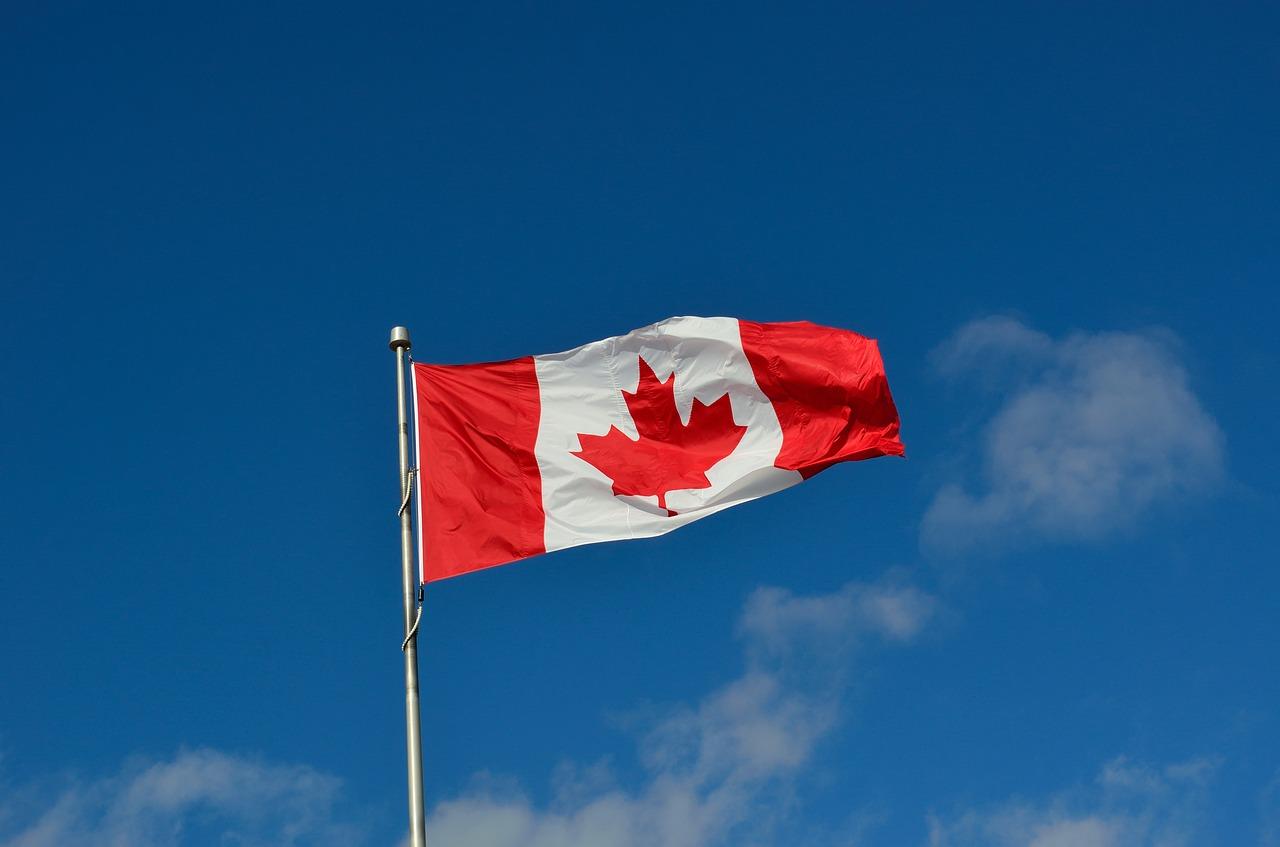 bandeira do Canadá flamulando no céu representando trabalhar e estudar no Canadá