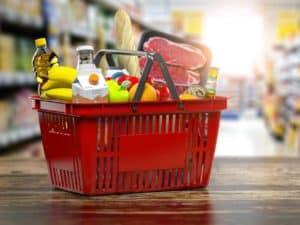 Cesta de supermercado com alimentos representando o aumento no preço dos alimentos.