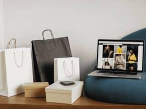 computador ao lado de várias sacolas, representando compras na china