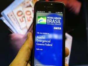 mão segurando celular com tela aberta no Caixa Tem representando contestação do auxílio emergencial 2021