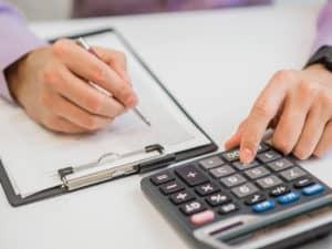 orçamento empresarial: imagem de uma pessoa usando uma calculadora e anotando no papel