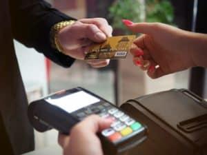 a imagem mostrar uma pessoa entregando um cartão para pagamentos para uma atendenentes. em segundo plano, aparece uma máquina de cartões. a cena simboliza a necessidade de mostrar CPF para descontos