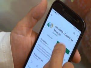 pessoa baixando aplicativo Meu INSS no celular representando prova de vida do INSS